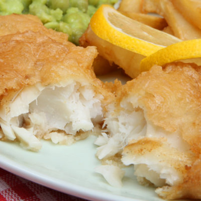 Deep fried battered cod fillet with chips and mushy peas
